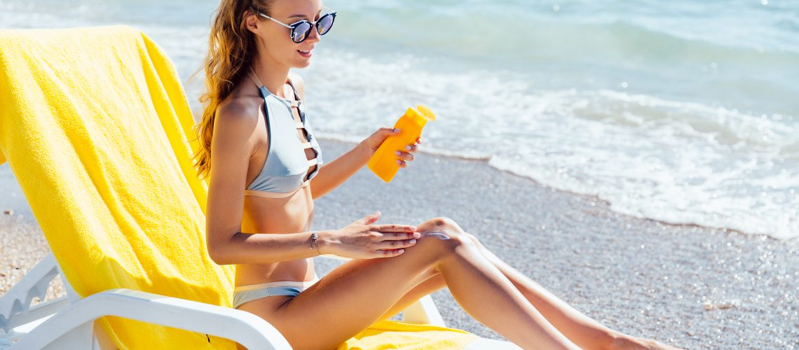 Attractive charming woman in swimsuit and sunglasses applying sun lotion on her legs, sitting on lounger, on the beach, near the sea.